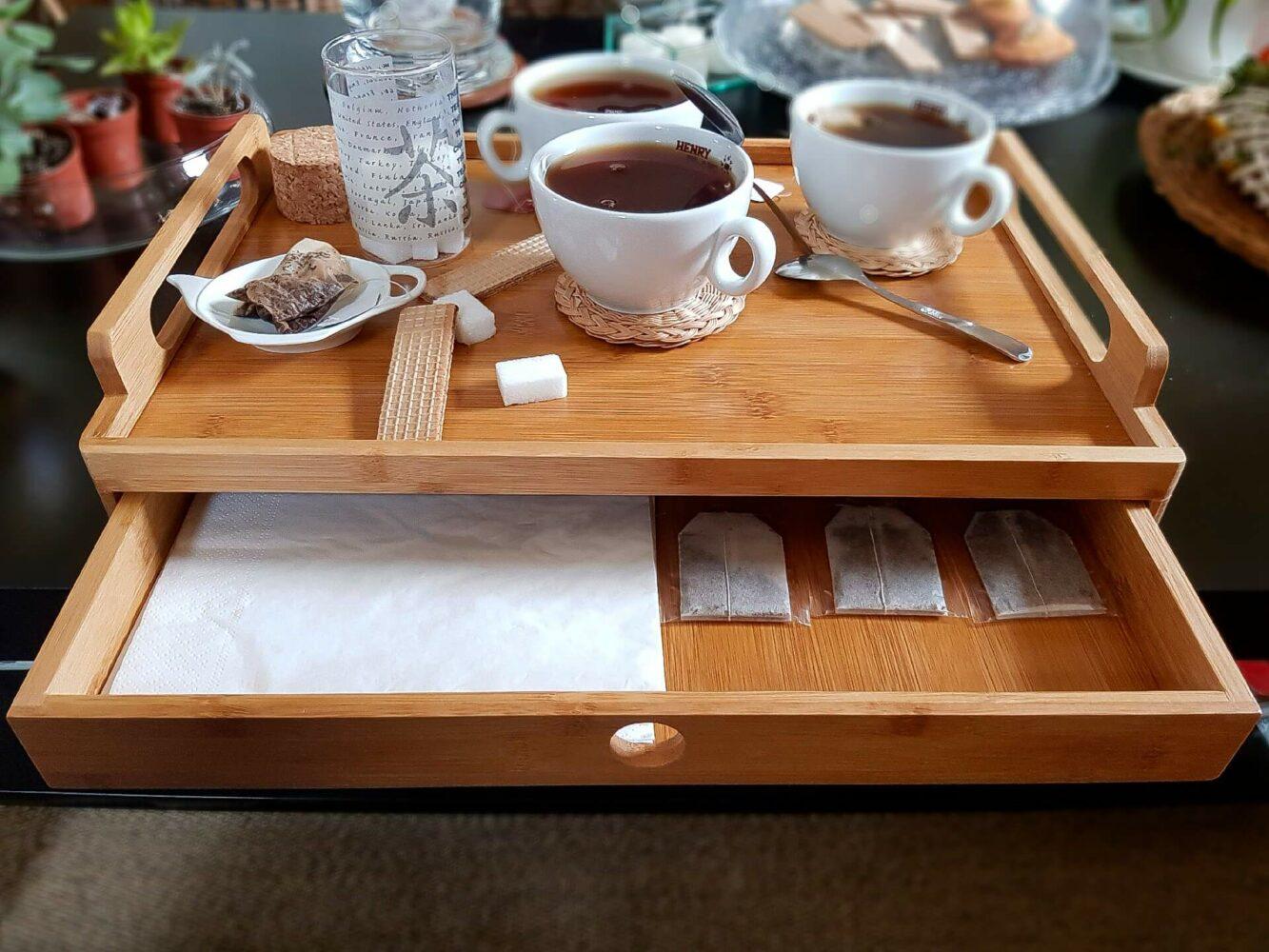 plateau de service en bambou équipé d'un tiroir posé sur une table