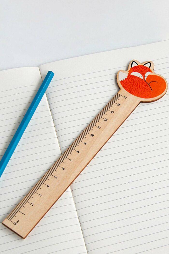 """règle en bois """"Rusty the fox"""" posé sur un cahier"""
